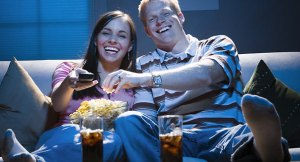 ADWDGT Couple sitting on sofa watching television with bowl of popcorn smiling