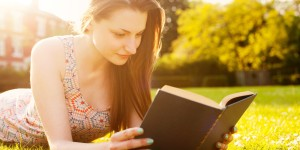 Young woman lying on grass reading book.